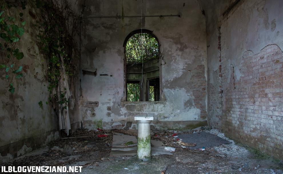 Veduta di un stretto corridoio pieno di materiale di risulta all'interno di un edificio di costruzione abbastanza recente, probabilmente facente parte dell'ospedale psichiatrico. (PH: Giacomo Martines)