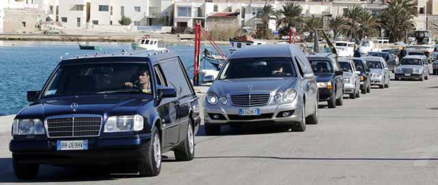 Hearses with the remains of migrants who died in a shipwreck arrive at the Lampedusa harbour