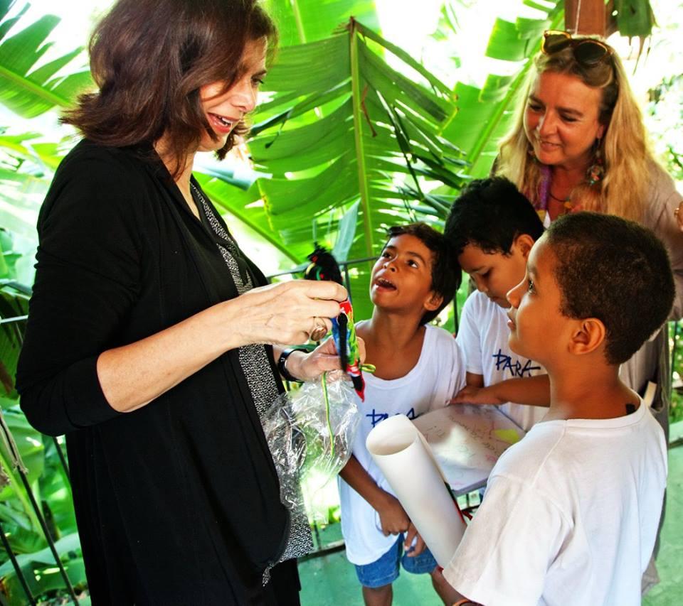 Laura Boldrini e Lidia Urani con alcuni bambini di Para Ti che danno alla Presidente i loro disegni