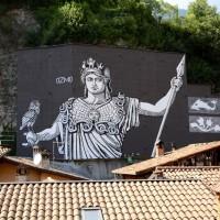 OZMO, al secolo Gionata Gesi, uno dei padri fondatori della Street Art italiana, ha realizzato il suo personale omaggio a Minerva, La MINERVA di OZMO si trova a BRENO (BS) in Piazza Gen. Ronchi, meglio conosciuta come Piazza del Mercato, sovrastata da uno splendido castello medievale che protegge la Valle Camonica, la Valle dei Segni.