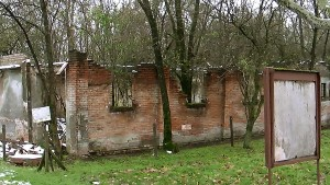 A building at the entrance to the Fossoli Concentration Camp is overrun with vegetation