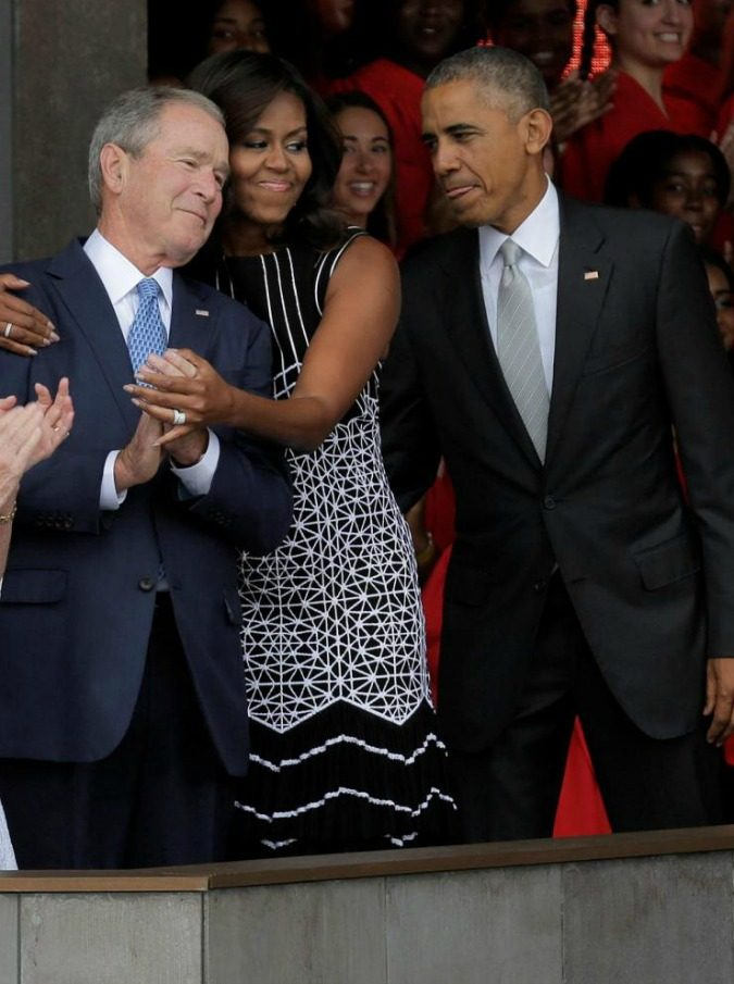 U.S. First Lady Michelle Obama hugs former U.S. President George W. Bush as she arrives with U.S. President Barack Obama and former first lady Laura Bush for the dedication of the Smithsonian's National Museum of African American History and Culture in Washington, U.S., September 24, 2016.      REUTERS/Joshua Roberts