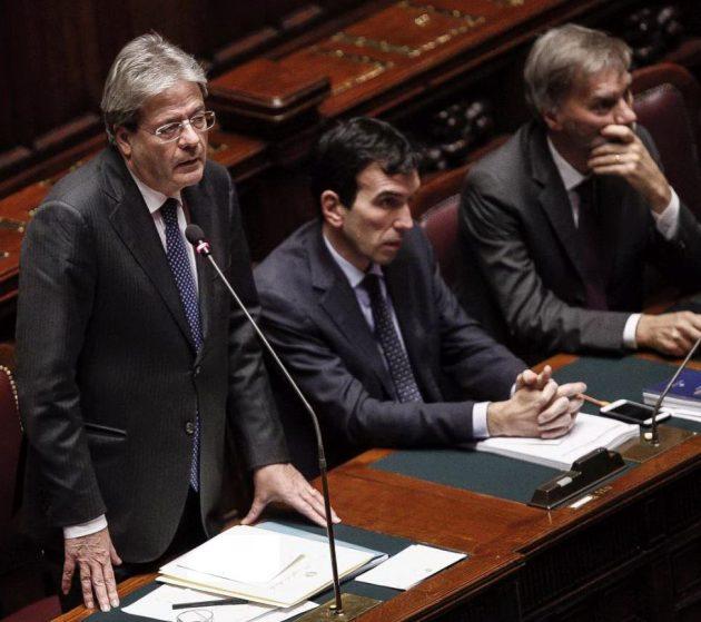 Paolo Gentiloni durante il suo intervento alla Camera. Al suo fianco i ministri all'Agricoltura e ai Trasporti Martina e Delrio