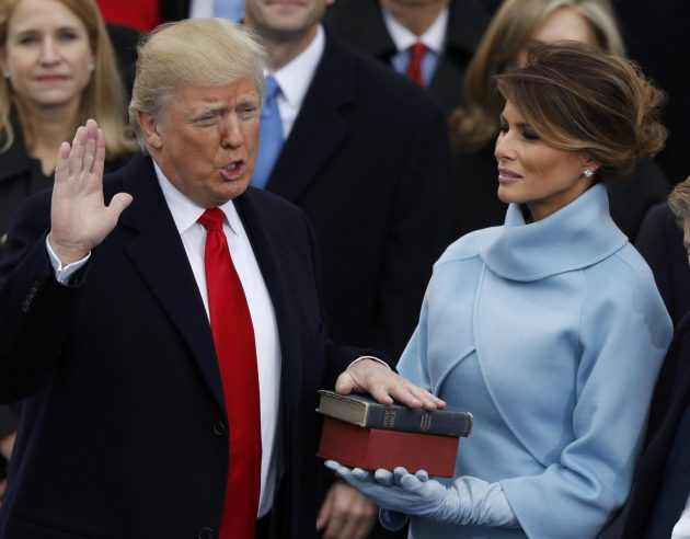 Donald Trump takes the oath of office as his wife Melania holds a bible during his inauguration as the 45th president of the United States on the West front of the U.S. Capitol in Washington, U.S., January 20, 2017. REUTERS/Lucy Nicholson