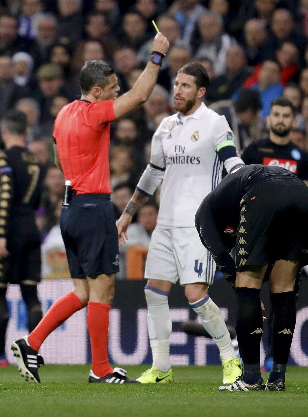 Slovenian referee Damir Skomina (L) gives a yellow card to Real Madrid's defender Sergio Ramos during the UEFA Champions League round of 16 match between Real Madrid and Napoli at Santiago Bernabeu stadium in Madrid, Spain, 15 February 2017. EFE/JuanJo Martin