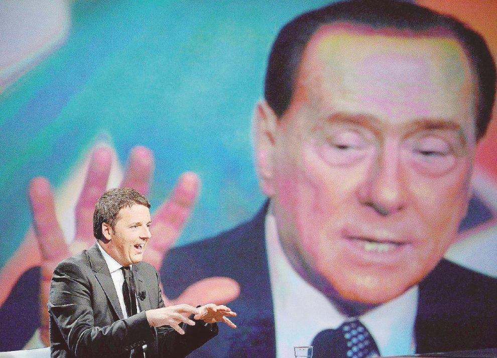 Il vecchio e il giovane – Matteo Renzi in uno studio televisivo. Alle spalle,  la gigantografia di Silvio Berlusconi –  Ansa