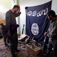 Membri delle Sdf ispezionano armi e munizioni trovate in un rifugio Isis