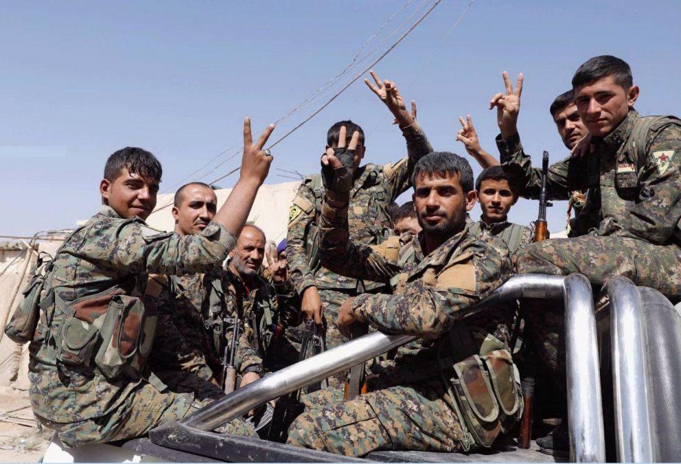 Combattenti delle Forze Democratiche Siriane fanno il segno della vittoria