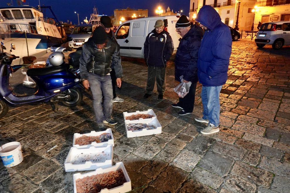 Si compra il pesce appena portato dai pescatori sulla piazza Aldo Moro.
