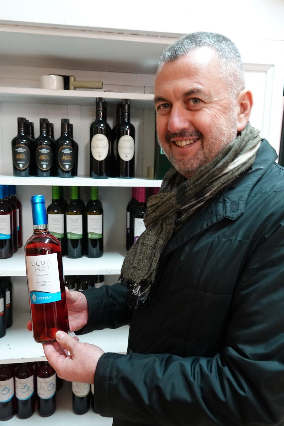Giuseppe Coppola con una bottiglia dei suoi vini pregiati.
