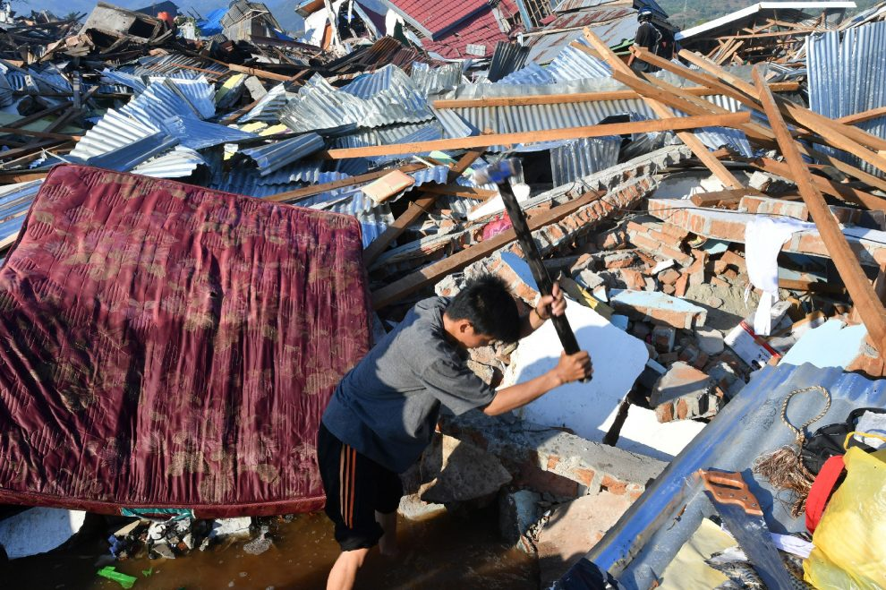 An Indonesian man breaks rubbles as he searches for a family member at their damaged house in the Balaroa village in Palu, Indonesia's Central Sulawesi on October 1, 2018. – The death toll nearly doubled to 832 but was expected to rise further after a disaster that has left the island of Sulawesi reeling. (Photo by ADEK BERRY / AFP)