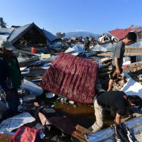 Indonesian men search for a family member at their damaged house in the Balaroa village in Palu, Indonesia's Central Sulawesi on October 1, 2018. – The death toll nearly doubled to 832 but was expected to rise further after a disaster that has left the island of Sulawesi reeling. (Photo by ADEK BERRY / AFP)