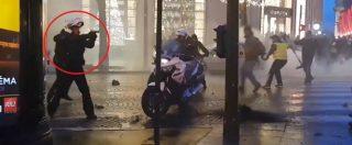 Gilet gialli, guerriglia in strada: poliziotto estrae la pistola e la punta contro i manifestanti. Forze dell'ordine in fuga