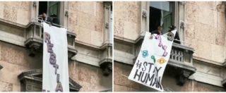 """Uomo vestito da Zorro espone striscione """"Restiamo umani"""" da un balcone in Duomo: rimosso tra fischi e proteste"""