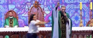 Il sacerdote sta celebrando la messa ma una donna sale sul palco e lo butta giù. E lui reagisce così