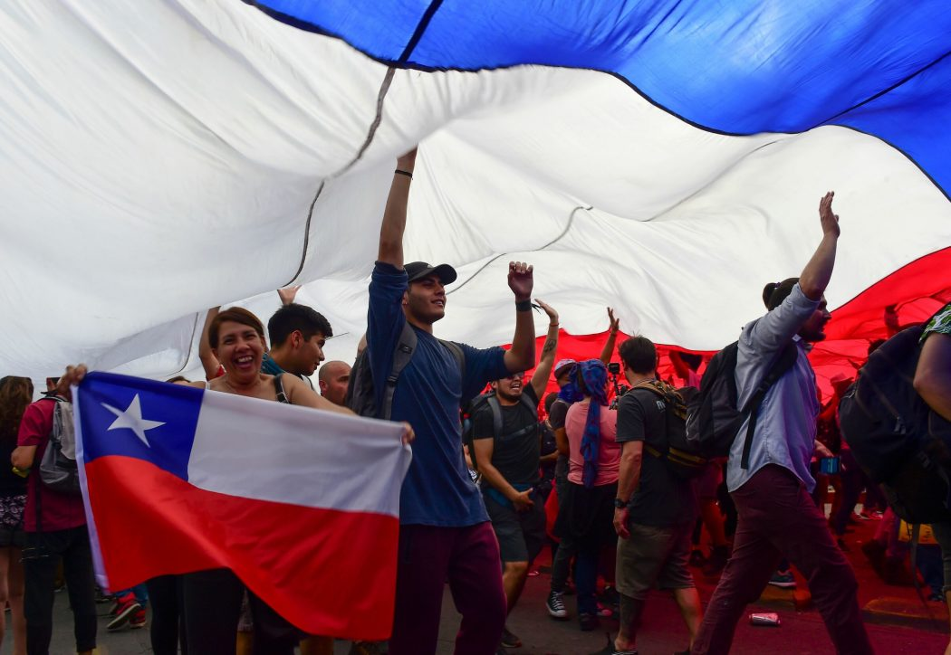 People protest under a giant Chilean natioonal flag in Santiago, on October 25, 2019, a week after violence protests started. – Demonstrations against a hike in metro ticket prices in Chile's capital exploded into violence on October 18, unleashing widening protests over living costs and social inequality. (Photo by Martin BERNETTI / AFP)