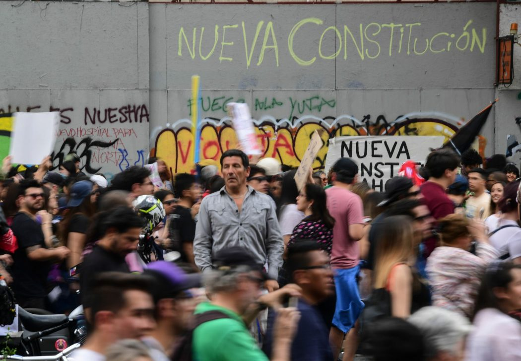 "People protest in front of a wall reading ""New Constitution"" in Santiago, on October 25, 2019, a week after violence protests started. – Demonstrations against a hike in metro ticket prices in Chile's capital exploded into violence on October 18, unleashing widening protests over living costs and social inequality. (Photo by Martin BERNETTI / AFP)"