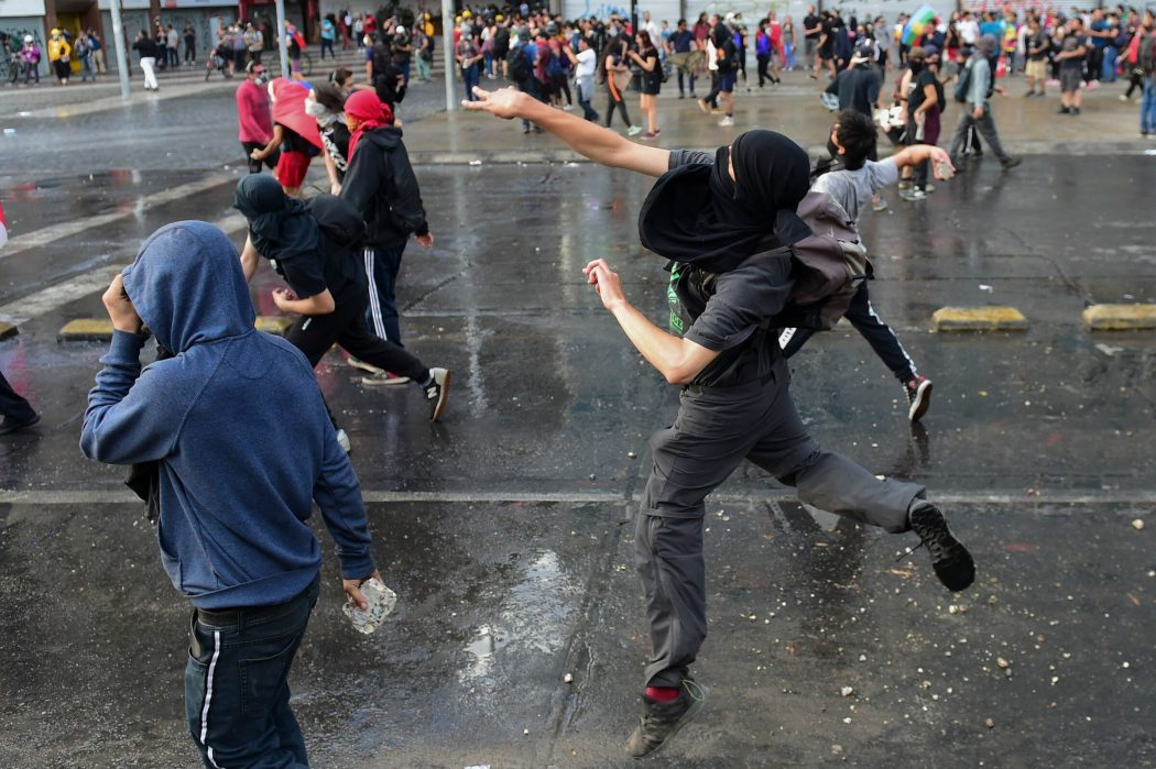 Demonstrators clash with the police in Santiago, on October 25, 2019, a week after violence protests started. – Demonstrations against a hike in metro ticket prices in Chile's capital exploded into violence on October 18, unleashing widening protests over living costs and social inequality. (Photo by Martin BERNETTI / AFP)