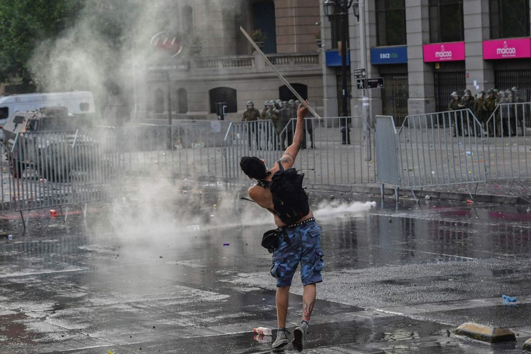 A demonstrator clashes with the police in Santiago, on October 25, 2019, a week after violence protests started. – Demonstrations against a hike in metro ticket prices in Chile's capital exploded into violence on October 18, unleashing widening protests over living costs and social inequality. (Photo by Martin BERNETTI / AFP)