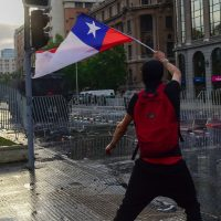 A demonstrator flutters a Chilean national flag during clashes with the police in Santiago, on October 25, 2019, a week after violence protests started. – Demonstrations against a hike in metro ticket prices in Chile's capital exploded into violence on October 18, unleashing widening protests over living costs and social inequality. (Photo by Martin BERNETTI / AFP)