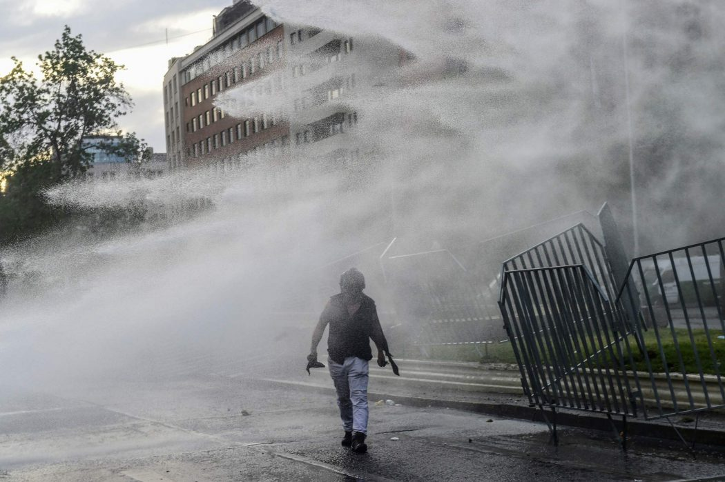 A demonstrator is sprayed water by the police in Santiago, on October 25, 2019, a week after violence protests started. – Demonstrations against a hike in metro ticket prices in Chile's capital exploded into violence on October 18, unleashing widening protests over living costs and social inequality. (Photo by Martin BERNETTI / AFP)