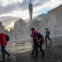 Demonstrators are sprayed water by the police in Santiago, on October 25, 2019, a week after violence protests started. – Demonstrations against a hike in metro ticket prices in Chile's capital exploded into violence on October 18, unleashing widening protests over living costs and social inequality. (Photo by Martin BERNETTI / AFP)