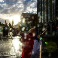 A man wrapped in the Chilean national flag demonstrates in front of police in Santiago, on October 25, 2019, a week after violence protests started. – Demonstrations against a hike in metro ticket prices in Chile's capital exploded into violence on October 18, unleashing widening protests over living costs and social inequality. (Photo by Martin BERNETTI / AFP)