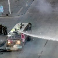 A man demonstrates with a Chilean national flag in front of a police vehicle spraying water in Santiago, on October 25, 2019, a week after violence protests started. – Demonstrations against a hike in metro ticket prices in Chile's capital exploded into violence on October 18, unleashing widening protests over living costs and social inequality. (Photo by Martin BERNETTI / AFP)