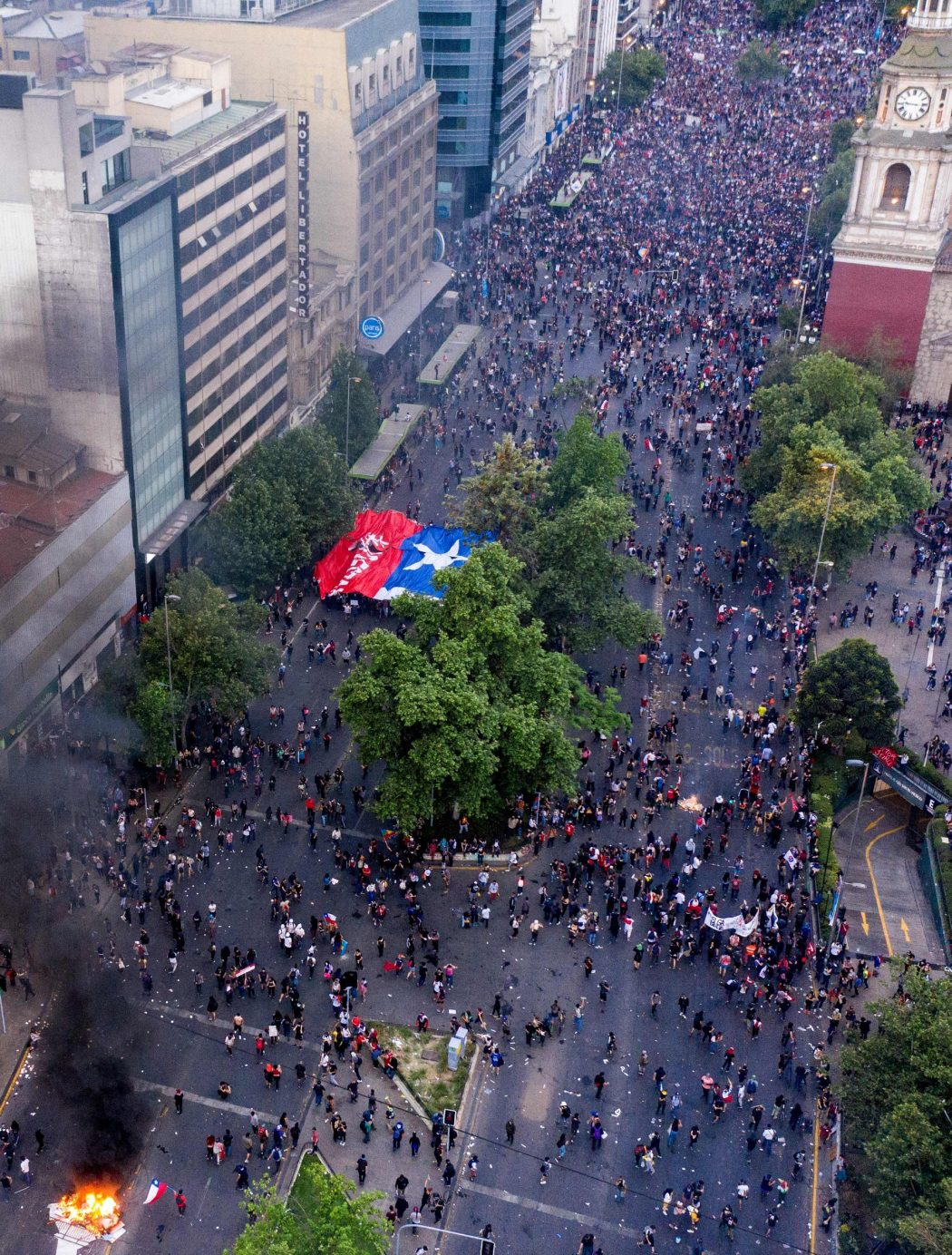Aerial view of people demonstrating in Santiago, on October 25, 2019, a week after violence protests started. – Demonstrations against a hike in metro ticket prices in Chile's capital exploded into violence on October 18, unleashing widening protests over living costs and social inequality. (Photo by PABLO COZZAGLIO / AFP)
