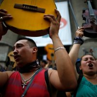 "Demonstrators hold up their instruments after performing Chilean musician Victor Jara's ""The right to live in peace"" in Santiago, on October 25, 2019, a week after violence protests started. – Demonstrations against a hike in metro ticket prices in Chile's capital exploded into violence on October 18, unleashing widening protests over living costs and social inequality. (Photo by Pablo VERA / AFP)"