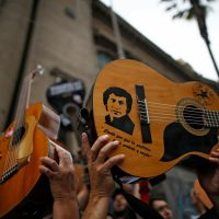 "Demonstrators hold up their guitards after performing Chilean musician Victor Jara's (depicted) ""The right to live in peace"" in Santiago, on October 25, 2019, a week after violence protests started. – Demonstrations against a hike in metro ticket prices in Chile's capital exploded into violence on October 18, unleashing widening protests over living costs and social inequality. (Photo by Pablo VERA / AFP)"