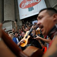 "Demonstrators play the guitar performing Chilean musician Victor Jara's ""The right to live in peace"" in Santiago, on October 25, 2019, a week after violence protests started. – Demonstrations against a hike in metro ticket prices in Chile's capital exploded into violence on October 18, unleashing widening protests over living costs and social inequality. (Photo by Pablo VERA / AFP)"