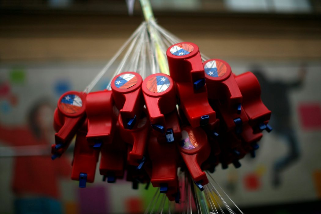 Whistles with the Chilean national flag are displayed for sale on a street of Santiago, on October 25, 2019, a week after violence protests started. – Demonstrations against a hike in metro ticket prices in Chile's capital exploded into violence on October 18, unleashing widening protests over living costs and social inequality. (Photo by Pablo VERA / AFP)