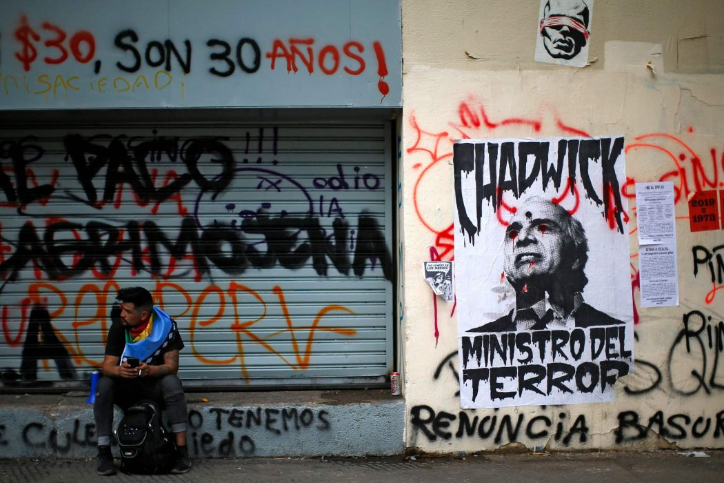 "A demonstrator wrapped in a Mapuche indigenous flag sits near a poster depicting Chilean Minister of Interior and Public Security Andres Chadwick reading ""Terror Minister"" in Santiago, on October 25, 2019, a week after violence protests started. – Demonstrations against a hike in metro ticket prices in Chile's capital exploded into violence on October 18, unleashing widening protests over living costs and social inequality. (Photo by Pablo VERA / AFP)"