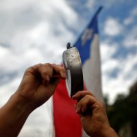 A demonstrator bangs a pot in front of a Chilean national flag in Santiago, on October 25, 2019, a week after violence protests started. – Demonstrations against a hike in metro ticket prices in Chile's capital exploded into violence on October 18, unleashing widening protests over living costs and social inequality. (Photo by Pablo VERA / AFP)
