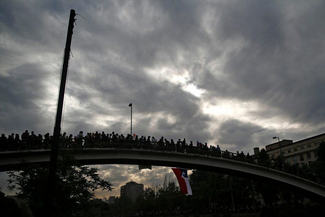 People demonstrate with a Chilean national flag in Santiago, on October 25, 2019, a week after violence protests started. – Demonstrations against a hike in metro ticket prices in Chile's capital exploded into violence on October 18, unleashing widening protests over living costs and social inequality. (Photo by Pablo VERA / AFP)