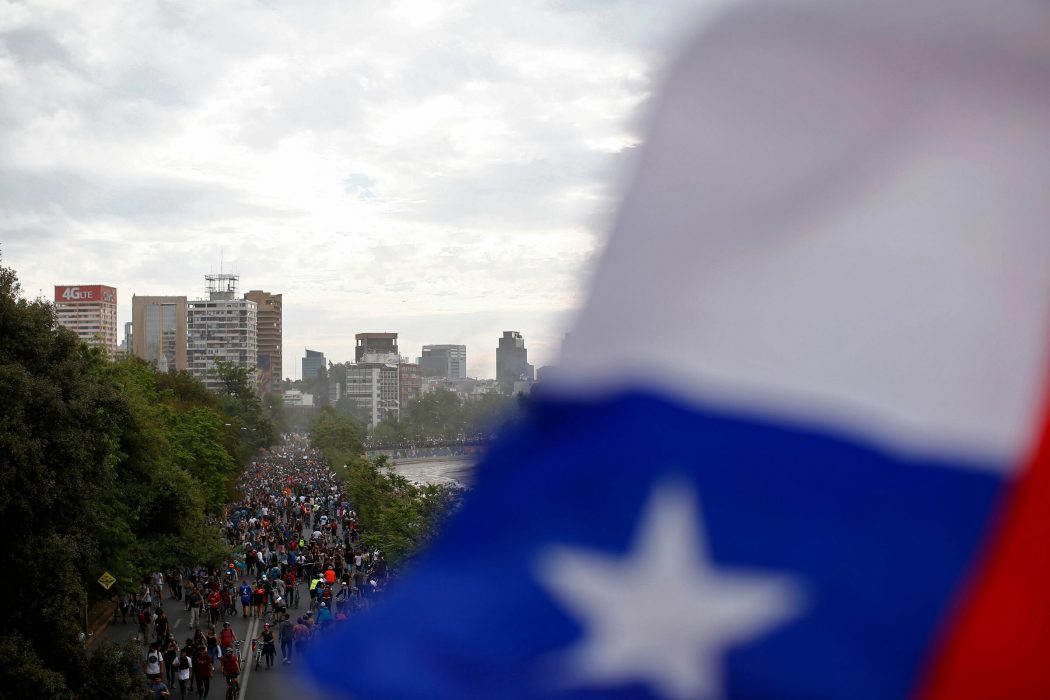 Aerial view of people demonstrating in Santiago, on October 25, 2019, a week after violence protests started. – Demonstrations against a hike in metro ticket prices in Chile's capital exploded into violence on October 18, unleashing widening protests over living costs and social inequality. (Photo by Pablo VERA / AFP)
