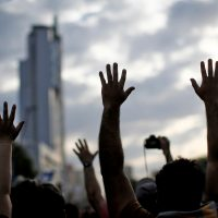 People raise their hands as they demonstrate in Santiago, on October 25, 2019, a week after violence protests started. – Demonstrations against a hike in metro ticket prices in Chile's capital exploded into violence on October 18, unleashing widening protests over living costs and social inequality. (Photo by Pablo VERA / AFP)