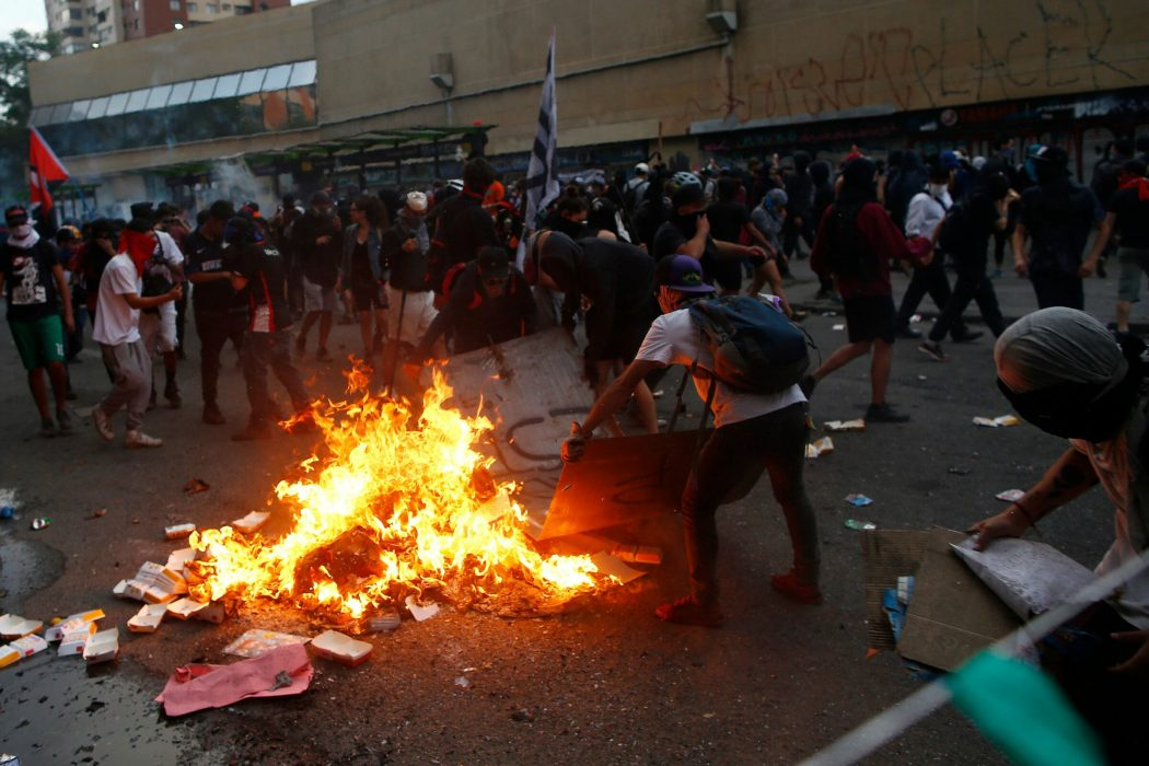 Demonstrators make a bonfire in Santiago, on October 25, 2019, a week after violence protests started. – Demonstrations against a hike in metro ticket prices in Chile's capital exploded into violence on October 18, unleashing widening protests over living costs and social inequality. (Photo by Pablo VERA / AFP)
