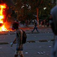 Demonstrators walk near a bonfire in Santiago, on October 25, 2019, a week after violence protests started. – Demonstrations against a hike in metro ticket prices in Chile's capital exploded into violence on October 18, unleashing widening protests over living costs and social inequality. (Photo by Pablo VERA / AFP)