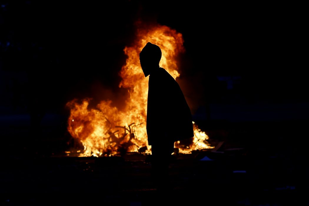 A demonstrator walks in front of a bonfire in Santiago, on October 25, 2019, a week after violence protests started. – Demonstrations against a hike in metro ticket prices in Chile's capital exploded into violence on October 18, unleashing widening protests over living costs and social inequality. (Photo by Pablo VERA / AFP)