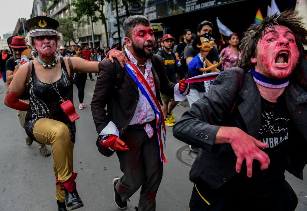 Disguised demonstrators take part in a protest in Santiago, on October 25, 2019, a week after violent protests started. – Demonstrations against a hike in metro ticket prices in Chile's capital exploded into violence on October 18, unleashing widening protests over living costs and social inequality. (Photo by MARTIN BERNETTI / AFP)