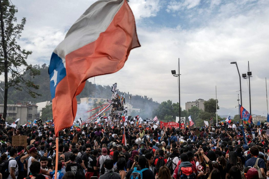 People demonstrate with a Chilean national flag in Santiago, on October 25, 2019, a week after protests started. – Demonstrations against a hike in metro ticket prices in Chile's capital exploded into violence on October 18, unleashing widening protests over living costs and social inequality. (Photo by Pedro Ugarte / AFP)
