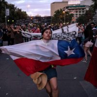 A demonstrator dances with a Chilean national flag in Santiago, on October 25, 2019, a week after protests started. – Demonstrations against a hike in metro ticket prices in Chile's capital exploded into violence on October 18, unleashing widening protests over living costs and social inequality. (Photo by Pedro Ugarte / AFP)