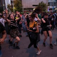 Demonstrators dance in Santiago, on October 25, 2019, a week after protests started. – Demonstrations against a hike in metro ticket prices in Chile's capital exploded into violence on October 18, unleashing widening protests over living costs and social inequality. (Photo by Pedro Ugarte / AFP)