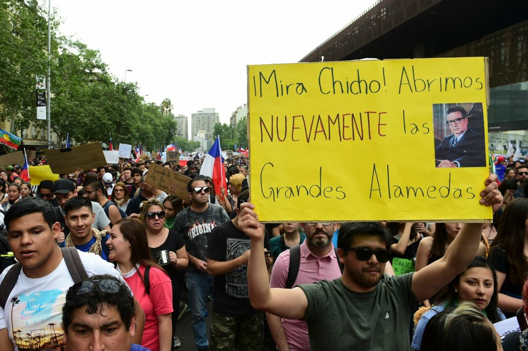 People demonstrate with a sign depicting Chilean late president (1970-73) Salvador Allende in Santiago, on October 25, 2019, a week after violence protests started. – Demonstrations against a hike in metro ticket prices in Chile's capital exploded into violence on October 18, unleashing widening protests over living costs and social inequality. (Photo by Martin BERNETTI / AFP)