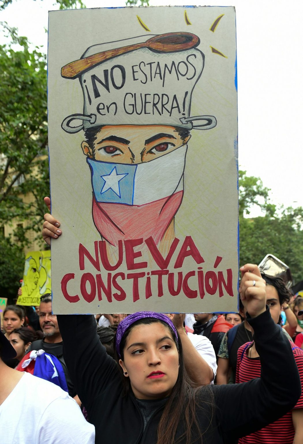 "A demonstrator holds a sign reading ""we are not in war. New Constitution"" in Santiago, on October 25, 2019, a week after violence protests started. – Demonstrations against a hike in metro ticket prices in Chile's capital exploded into violence on October 18, unleashing widening protests over living costs and social inequality. (Photo by Martin BERNETTI / AFP)"