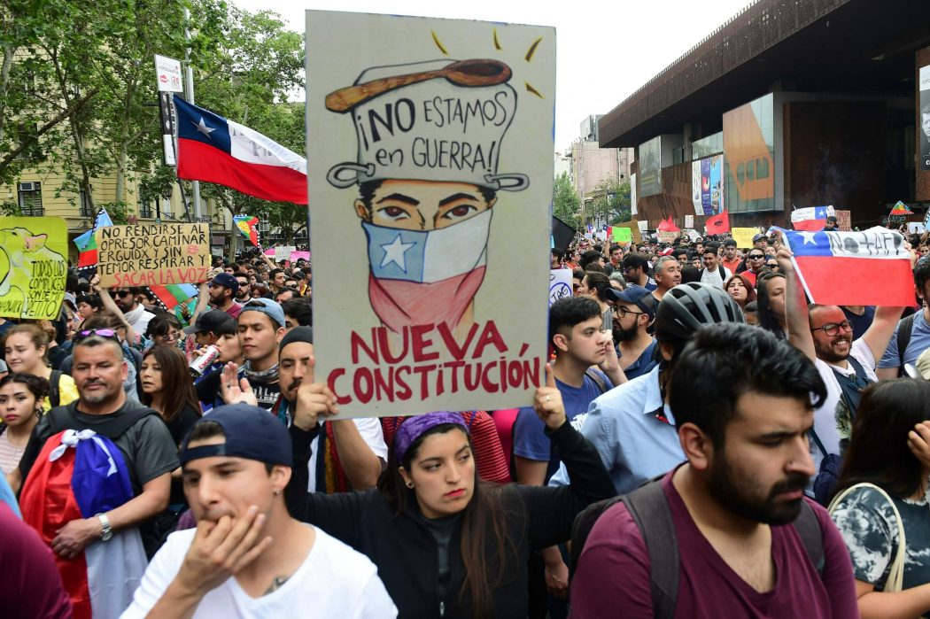 "People protest with a sign reading ""we are not in war. New Constitution"" in Santiago, on October 25, 2019, a week after violence protests started. – Demonstrations against a hike in metro ticket prices in Chile's capital exploded into violence on October 18, unleashing widening protests over living costs and social inequality. (Photo by Martin BERNETTI / AFP)"