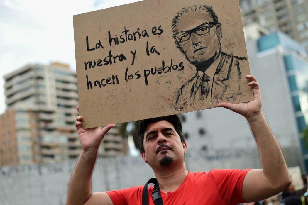 "A man holds a sign depicting Chilean late President (1970-73) Salvador Allende reading ""History is ours and people make it"" in Santiago, on October 25, 2019, a week after violence protests started. – Demonstrations against a hike in metro ticket prices in Chile's capital exploded into violence on October 18, unleashing widening protests over living costs and social inequality. (Photo by Martin BERNETTI / AFP)"