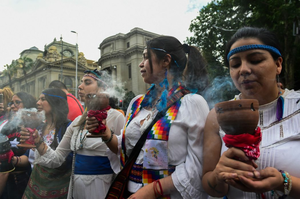 Women demonstrate with incense in Santiago, on October 25, 2019, a week after violence protests started. – Demonstrations against a hike in metro ticket prices in Chile's capital exploded into violence on October 18, unleashing widening protests over living costs and social inequality. (Photo by Martin BERNETTI / AFP)